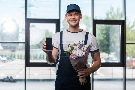 Photo pour Heureux livreur tenant bouquet de fleurs en fleurs et smartphone avec écran blanc - image libre de droit