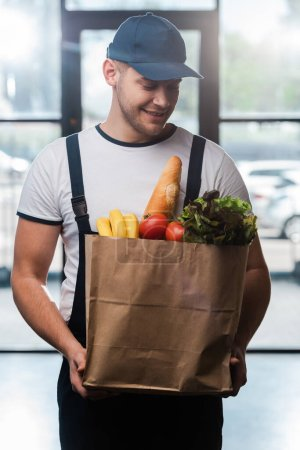 happy delivery man in cap looking at paper bag with groceries