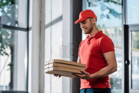 heureux livreur homme en chapeau regardant les boîtes à pizza