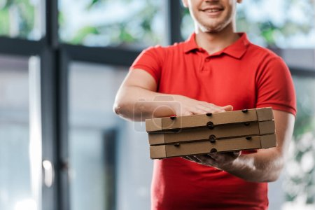 Photo for Cropped view of smiling delivery man holding pizza boxes - Royalty Free Image