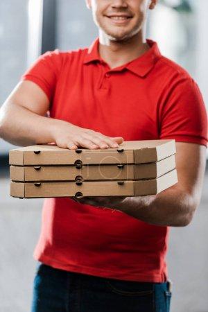 Photo pour Vue recadrée du livreur positif tenant des boîtes à pizza - image libre de droit