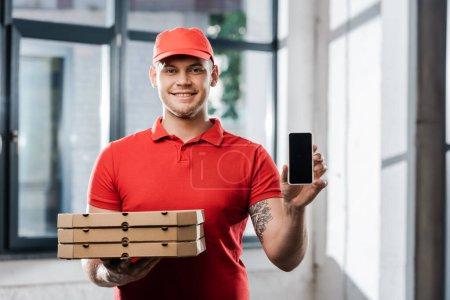 Photo pour Heureux livreur dans le chapeau tenant smartphone avec écran vierge et boîtes à pizza - image libre de droit