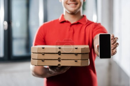Photo pour Vue recadrée du livreur heureux dans le chapeau tenant smartphone avec écran vierge et boîtes à pizza - image libre de droit