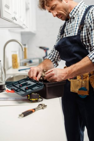 Photo for Selective focus of plumber holding handle of faucet near open toolbox in kitchen - Royalty Free Image