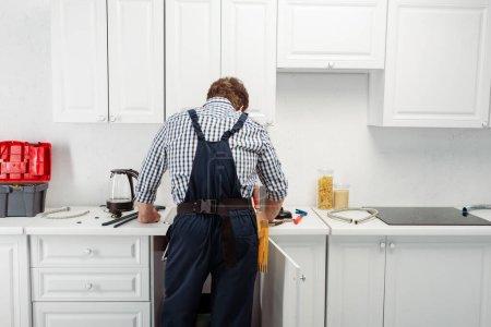Photo pour Vue arrière du plombier en salopette travaillant dans la cuisine - image libre de droit