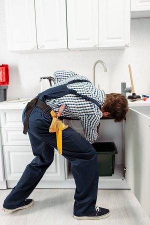 Back view of plumber in overalls fixing sink in kitchen