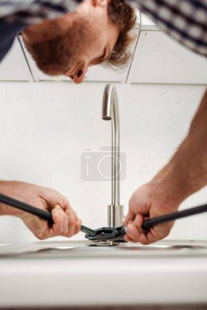 Photo pour Mise au point sélective de la clé à tuyau de maintien du plombier lors de la fixation du robinet de cuisine - image libre de droit