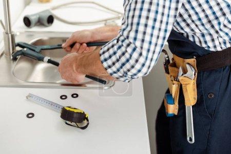 Photo pour Vue recadrée du robinet de fixation du réparateur avec clé à tuyau près des outils sur le plan de travail de la cuisine - image libre de droit