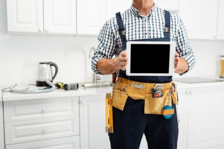 Photo for Cropped view of plumber in tool belt holding digital tablet in kitchen - Royalty Free Image