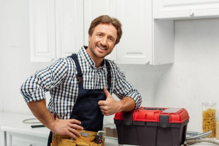 Photo for Handsome plumber showing like gesture and smiling at camera near toolbox in kitchen - Royalty Free Image