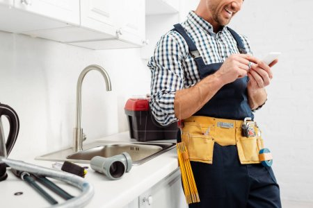 Cropped view of smiling plumber using smartphone near tools on kitchen worktop