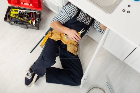 Photo for Top view of handyman in overalls and tool belt holding pliers while repairing sink in kitchen - Royalty Free Image