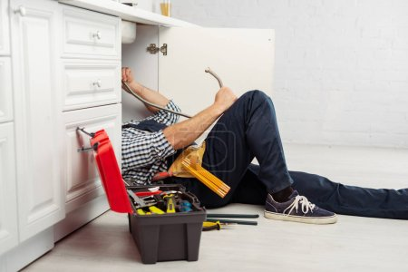 Selective focus of plumber holding metal pipe while fixing kitchen sink near instrument and toolbox in kitchen