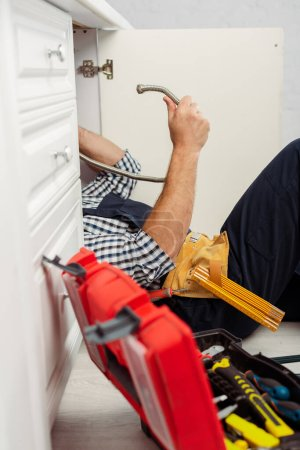 Selective focus of workman holding metal pipe near open toolbox while fixing kitchen sink