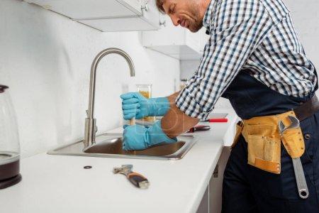 Photo pour Vue latérale du beau plombier dans la ceinture à outils et gants en caoutchouc nettoyage évier de cuisine avec piston - image libre de droit