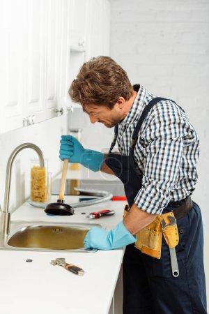 Photo pour Vue latérale du plombier en gants de caoutchouc tenant le piston lors de la fixation de l'évier de cuisine - image libre de droit