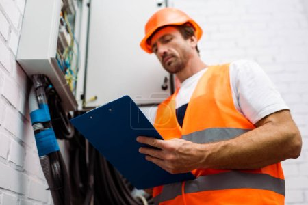 Photo for Selective focus of electrician in hardhat and safety vest holding clipboard near electric panel - Royalty Free Image
