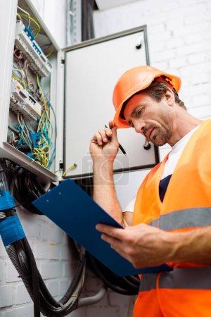 Foto de Enfoque selectivo de electricista guapo en pluma de sujeción de sombreros duros y mirando el portapapeles cerca del panel eléctrico. - Imagen libre de derechos