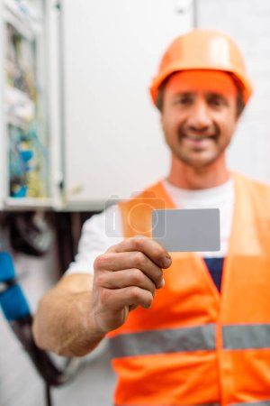 Photo for Selective focus of smiling electrician in hardhat holding empty card - Royalty Free Image
