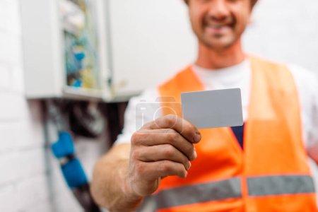 Foto de Enfoque selectivo de electricista en chaleco de seguridad con tarjeta vacía - Imagen libre de derechos