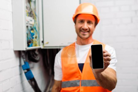 Photo for Selective focus of smiling electrician holding smartphone with blank screen near electrical distribution box - Royalty Free Image