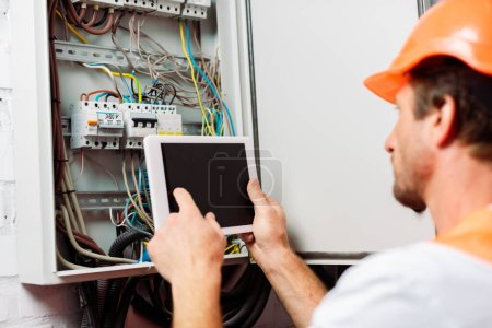 Photo for Selective focus of electrician using digital tablet with blank screen near electrical distribution box - Royalty Free Image