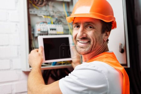 Photo for Selective focus of smiling electrician in hardhat holding digital tablet while working with electric panel - Royalty Free Image