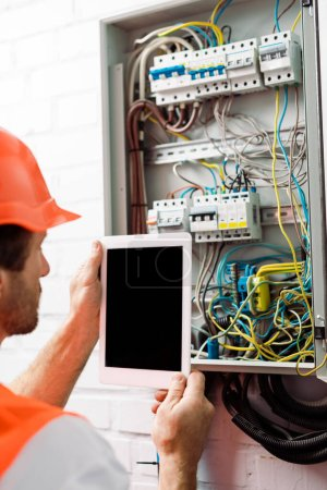 Photo for Selective focus of electrician holding digital tablet with blank screen near electrical distribution box - Royalty Free Image