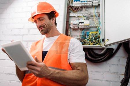 Photo pour Mise au point sélective du bel électricien utilisant une tablette numérique près de la boîte de distribution électrique - image libre de droit