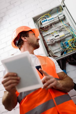 Photo for Selective focus of handsome electrician in hardhat looking at electrical distribution box while holding digital tablet - Royalty Free Image