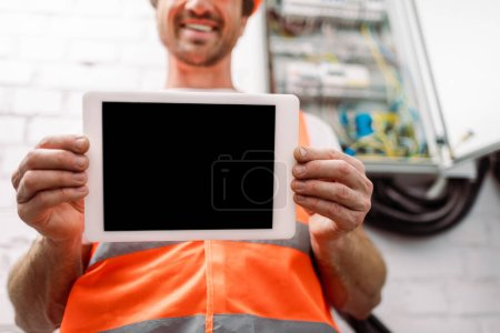 Photo for Cropped view of smiling electrician showing digital tablet with blank screen - Royalty Free Image