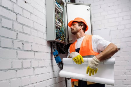 Photo for Handsome electrician holding blueprint near electrical distribution box - Royalty Free Image