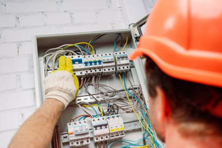 Photo for Selective focus of electrician turning on toggle switches of electrical distribution box - Royalty Free Image