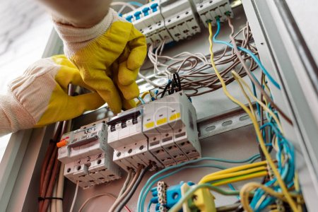 Photo for Low angle view of electrician in gloves fixing electrical distribution box - Royalty Free Image