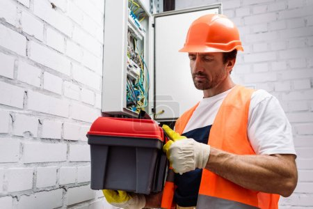 Photo for Handsome electrician holding toolbox near electrical distribution box - Royalty Free Image