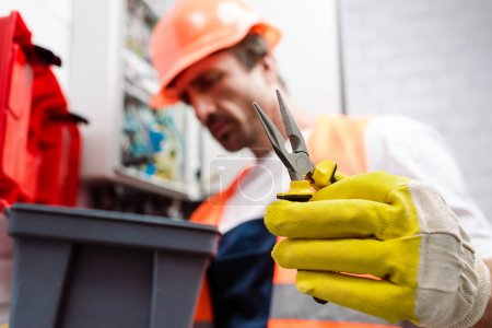 Photo for Selective focus of electrician in hardhat holding pliers near toolbox - Royalty Free Image