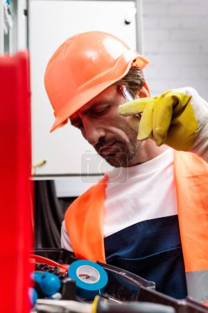 Photo for Selective focus of pensive electrician looking at tools in toolbox near electrical distribution box - Royalty Free Image