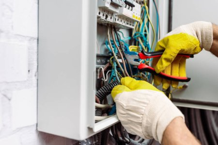 Photo for Cropped view of workman in gloves holding pliers while fixing electrical distribution box - Royalty Free Image