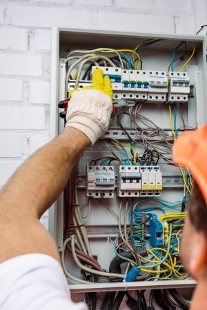 Photo for Selective focus of electrician in glove holding pliers and turning on toggle switches of electrical box - Royalty Free Image