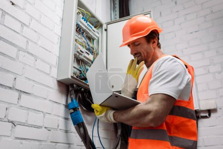 Photo for Side view of handsome electrician taking off glove while holding laptop near electric panel - Royalty Free Image