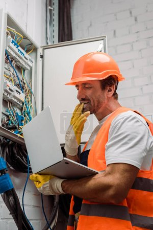 Photo for Side view of electrician taking off glove and holding laptop near electrical distribution box - Royalty Free Image