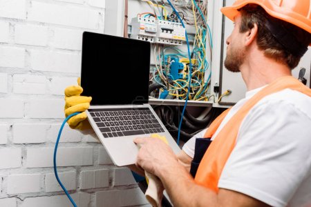 Photo for Selective focus of electrician using laptop near electrical distribution box - Royalty Free Image