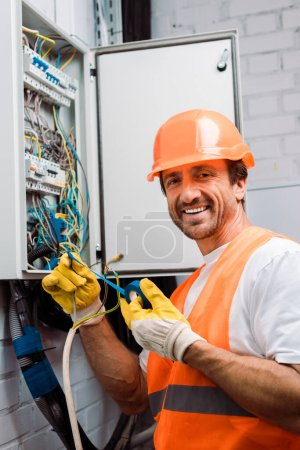 Photo for Smiling electrician holding insulating tape and wires while fixing electric panel - Royalty Free Image