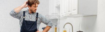 Photo pour Plombier pensif avec main près de la tête regardant le robinet dans la cuisine, orientation panoramique - image libre de droit