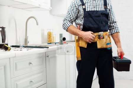 Photo for Cropped view of plumber in workwear holding toolbox near sink and faucet in kitchen - Royalty Free Image