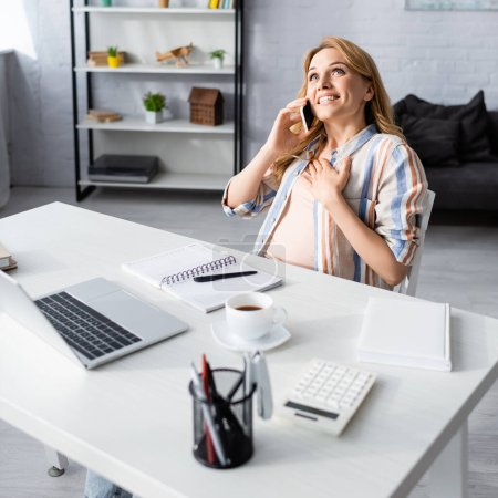 Selective focus of happy woman talking on smartphone near laptop, stationery and coffee on table