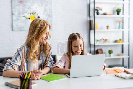 Photo pour Concentration sélective de sourire enfant en utilisant un ordinateur portable près de la mère pendant l'éducation en ligne - image libre de droit
