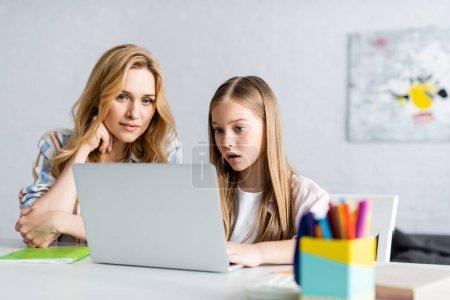 Photo pour Concentration sélective de la mère et de la fille regardant l'ordinateur portable pendant l'éducation en ligne à la maison - image libre de droit