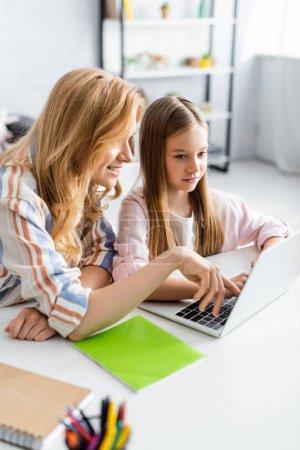 Photo pour Concentration sélective de la mère souriante utilisant un ordinateur portable près de sa fille pendant le webinaire à la maison - image libre de droit