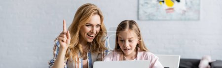 Photo for Panoramic shot of smiling woman having idea while helping daughter with online education - Royalty Free Image